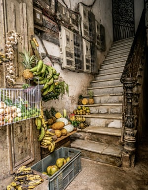 A dilapidated stairwell in the city centre, with fruit stacked on it
