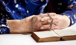 An elderly pair of hands holding a cross
