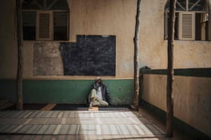 A man rests in the shade at the mosque in Pemba