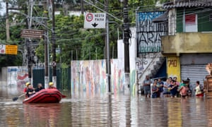 Residents walk in the middle of a flooded street after heavy rains in Sao Paulo, Brazil.