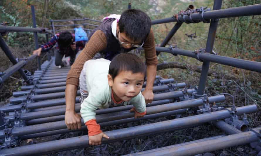 Children climb steel cliff ladders to get in and out of Atulie'er village, Sichuan province, China.