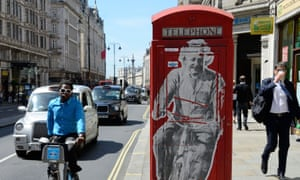 A graffiti poster of Einstein on a bike on a red phone box, on the Strand.