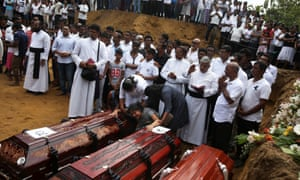 A woman weeps next to two coffins during a mass burial of victims at a cemetery near St. Sebastian Church in Negombo.