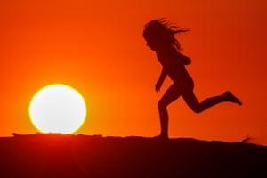 A child runs along the beach at sunset in Carlsbad, California, US