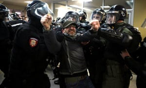 Serbian riot police scuffle with a protester who invaded the state TV building during an anti-government demonstration.