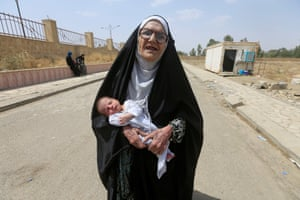 Mosul, IraqAn elderly displaced Iraqi woman who fled from Islamic State militants carries a baby