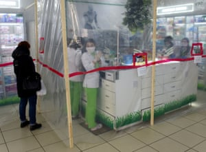 Pharmacists wearing face masks work behind polyethylene membrane set around the counter in a pharmacy in the western Ukrainian city of Lviv