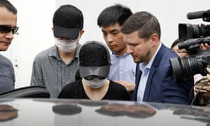 Unidentified Crown Resorts employees wearing face masks are escorted by security as they leave the Baoshan District People's Court after the trial on Monday.