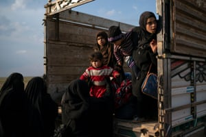 Women and children leave the back of a truck, part of a convoy evacuating hundreds out of the last territory held by Isis militants in Baghuz, eastern Syria