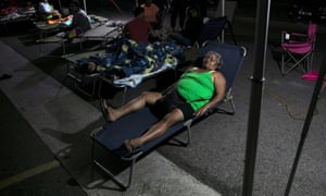 People rest at a makeshift camp outside their apartment building after an earthquake in Yauco, Puerto Rico.