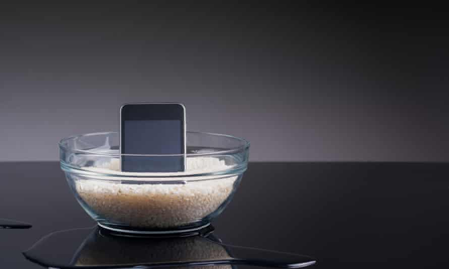 Drying rice<br>A conceptual image with a phone inside a bowl with rice and reflected on black, there is also some water on the floor.