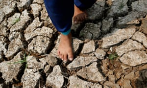 A boy walks on drought parched land.