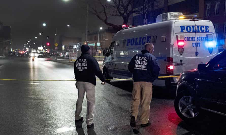 Police officers investigate at the scene where an officer shot and killed an armed man on Wednesday in Brooklyn, New York.