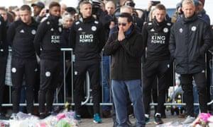 Aiyawatt Srivaddhanaprabha, the son of Vichai Srivaddhanaprabha, and players look at tributes left at the stadium