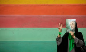 A supporter of the Iranian opposition leader, Mir Hossein Mousavi, hides her face behind his poster.