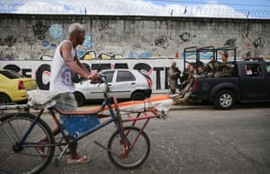 A favela resident walks past a vehicle carrying security forces. Residents claim the security forces held poor communities in a state of semi-siege, not 'to protect us, but to segregate us' from Olympic visitors