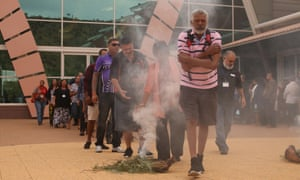 Ernie Dingo and other attendees walk through smoke to be cleansed at a ceremony to open Australia's first Indigenous suicide prevention conference in Alice Springs in 2016.