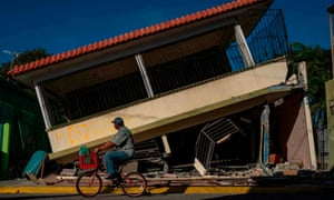 A man rides his bicycle pass by a collapsed house in Guanica, Puerto Rico on January 15, 2020, after a powerful earthquake hit the island.