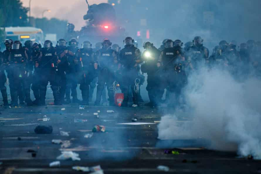 Police in riot gear block a road in Minneapolis.