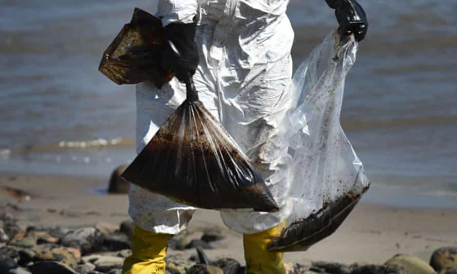 Workers clean oil from the rocks and beach at Refugio state beach in Goleta, California.