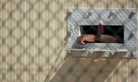 A detainee's arm hangs outside his cell at a security prison on the US naval station in Guantanamo Bay in 2005