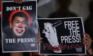Journalists and supporters display placards showing President Rodrigo Duterte as a clown