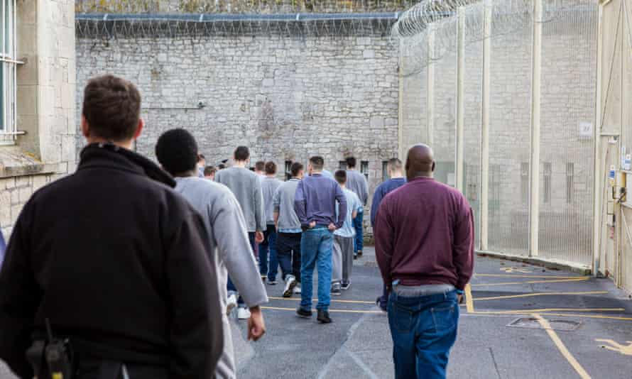 Prisoners escorted by officers move around HMP/YOI Portland