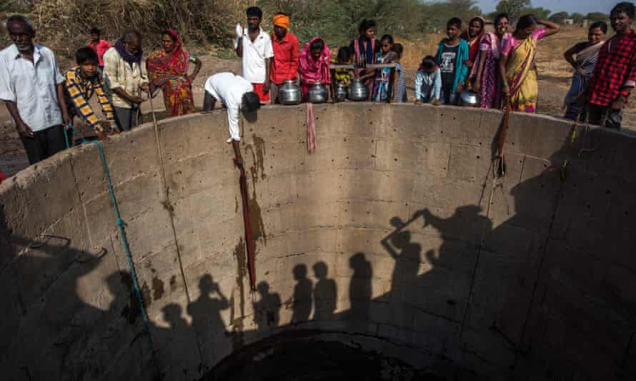 Villagers from Nandi village in Jaina, India, fill muddy water from the well.