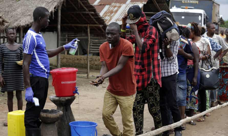 People in a village on the outskirts of Freetown leave Ebola quarantine, 12 August.