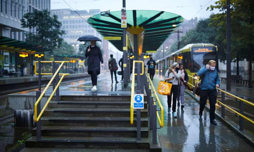 Commuters in and around St Peter's Square metrolink tram station in central Manchester.