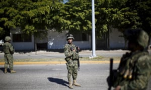 Soldiers stand outside the safe house on Jiquilpan boulevard, where five people were shot dead during the operation to recapture Joaquín 'El Chapo' Guzmán in Los Mochis, Mexico.
