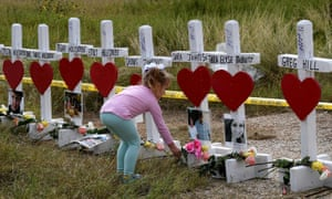 A child leaves flowers on crosses for victims of the First Baptist church shooting that killed 26 people in Sutherland Springs, Texas, on 9 November 2017.