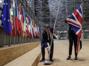 EU Council staff members remove the United Kingdom's flag from the European Council building in Brussels