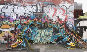 An unknown artist creates mural in a lane way in Melbourne, Australia from dockless bikes.