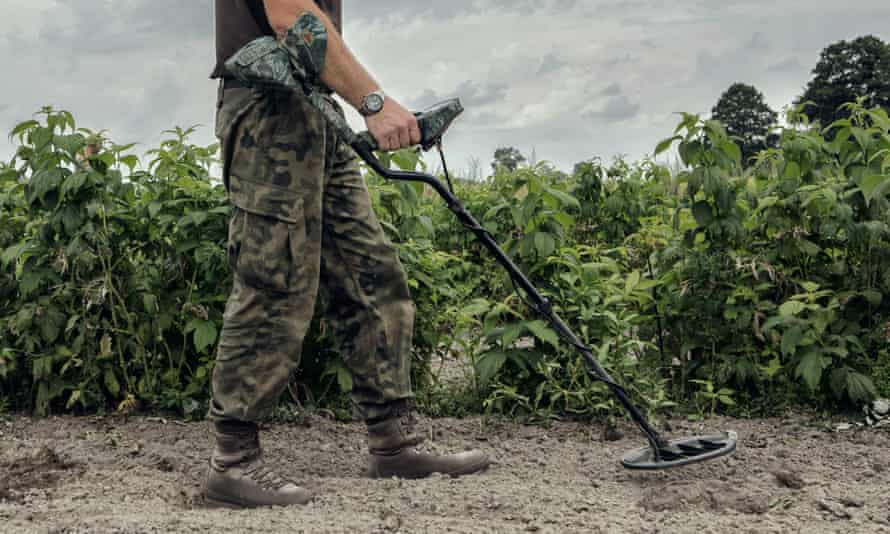 Metal detecting is a contentious issue within the heritage community. A man with a metal detector walks through a field of crops.