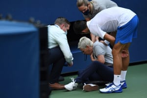 Novak Djokovic consoles a line judge after he accidentally hit her with a ball in a moment of frustration at the US Open, leading to his disqualification.