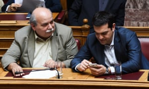 Greek prime minister, Alexis Tsipras (right), uses his phone next to the minister of interior, Nikos Voutsis