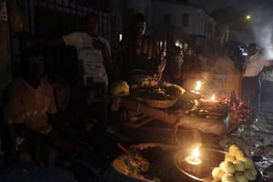 At another Lagos market, vegetable vendors ply their wares by the light of locally-made lanterns.