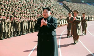 North Korean leader Kim Jong-un claps during a photo session with the participants of a meeting of military and political cadres in this undated photo released by North Korea's Korean Central News Agency (KCNA) in Pyongyang.