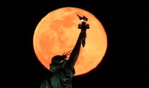 New York City, US. The full Snow Moon rises behind the Statue of Liberty in New York City, as seen from Jersey City, New Jersey