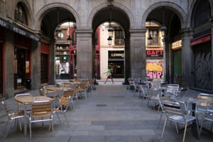 A woman wearing a face mask walks past empty terraces of bars at Plaza Reial in Barcelona, Spain.