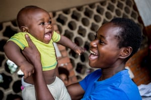 A mother holds up her child as she queues to register her birth at the Chipata clinic in Lusaka, Zambia