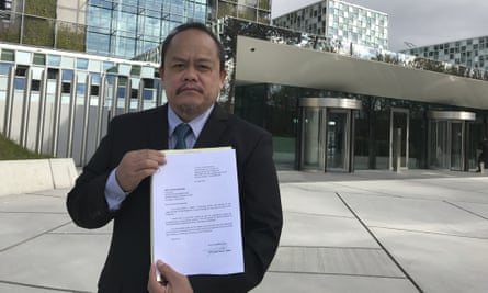 Lawyer Jude Sabio from the Philippines poses for a portrait as he holds a 77-page file outside the International Criminal Court in The Hague.
