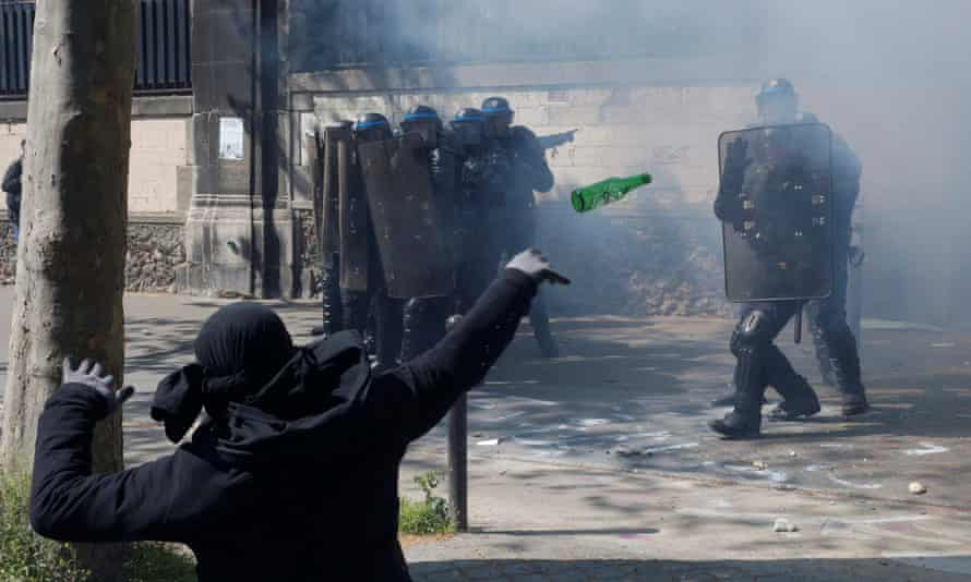 A protester throws a bottle towards police during clashes in Paris.