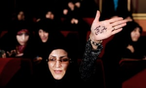 An Iranian raises her palm with writing in Persian