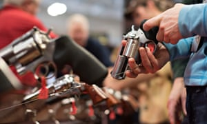 An attendee handles a revolver in the Sturm Ruger booth on the exhibition floor of the NRA's annual meeting in Nashville.