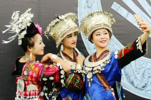 Young girls dress up in traditional costume and pose for a selfie at the opening ceremony of the Leishan Miao new year festival in the Chinese city of Kaili, Guizhou province