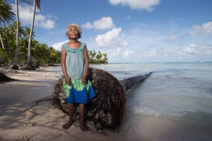 Maria Tekaie stands beside a fallen coconut tree where the sea has washed away the village of Tebontebike on the southern end of Abaiang.