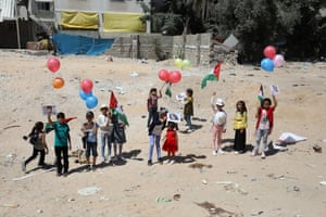 Palestinian children hold helium balloons on empty patch of land