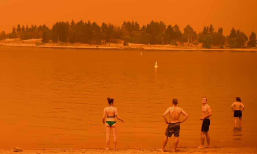 Residents take a dip to cool down at Lake Jindabyne under a red sky due to smoke from bushfires, in the town of Jindabyne in New South Wales on 4 January 2020.